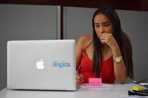 Mujer anotando en post it y observando el notebook