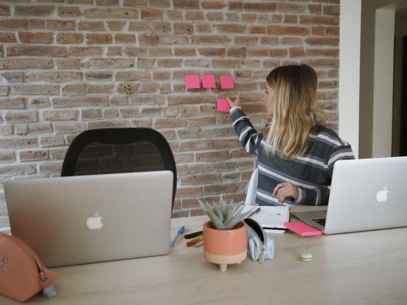 mujer trabajando en un notebook y colocando post it en una pared